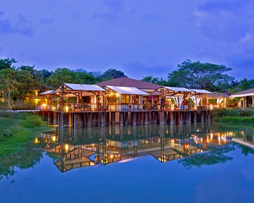Exterior view of Reserva Conchal Vacation Club alongside the waterfront at dusk.