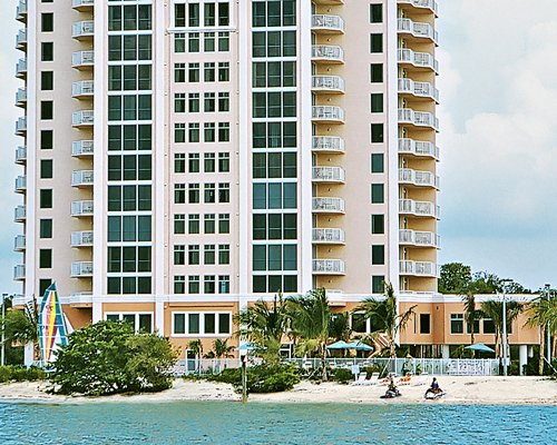 An exterior view of multi story resort units facing the beach.