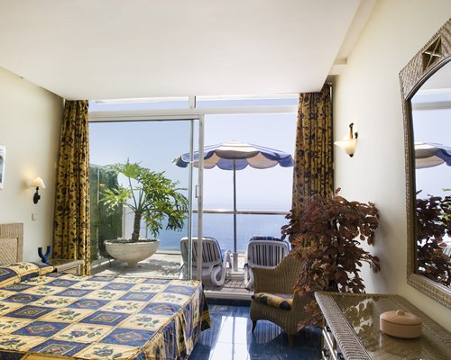 A well furnished bedroom with balcony chaise lounge chairs sunshade and ocean view.