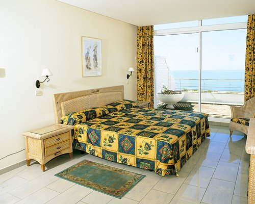 A well furnished bedroom and a balcony with the beach view.