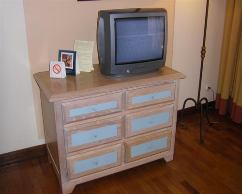 A television on a stand in a room with wooden floors.