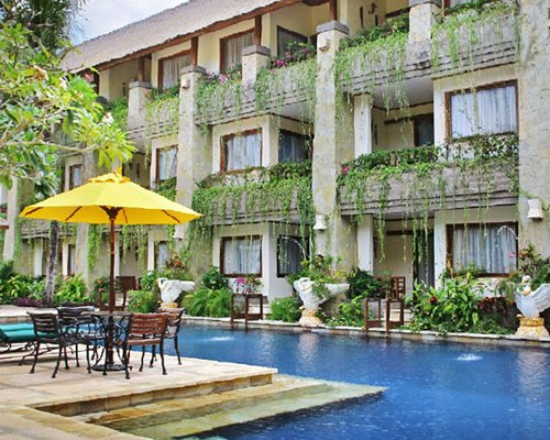 An exterior view of The Grand Bali  Nusa Dua resort with patio furniture.