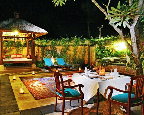 An outdoor fine dining with chaise lounge chairs and plants at night.