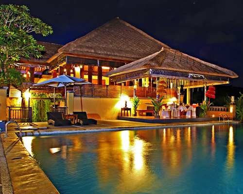 An outdoor swimming pool alongside resort units at dusk.