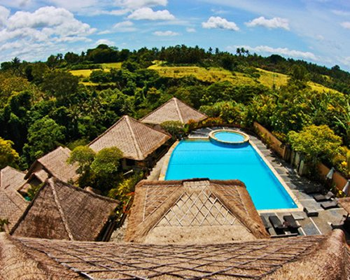 An outdoor swimming pool and hot tub alongside the resort surrounded by trees.