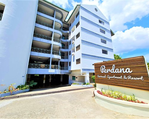 Multiple unit balconies with an outdoor swimming pool and palm trees.