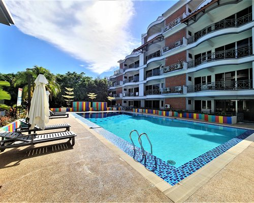 An outdoor swimming pool with patio alongside multi story units.