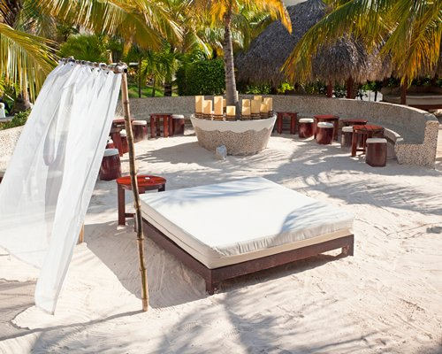 Outdoor lounge area with beach beds and palm trees.