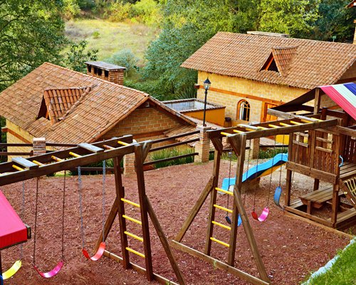 An outdoor playscape with swings alongside resort units.