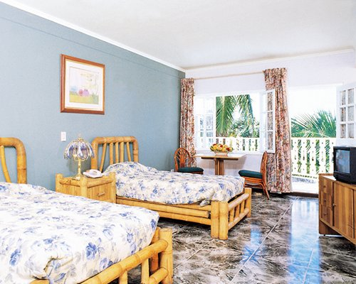 A well furnished bedroom with two twin beds television dining area and balcony.