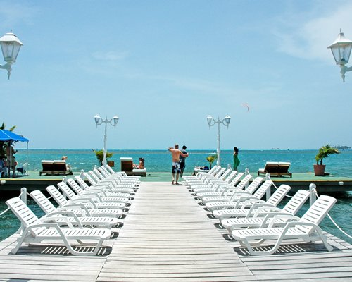 Wooden pier with chaise lounge chairs alongside the sea.