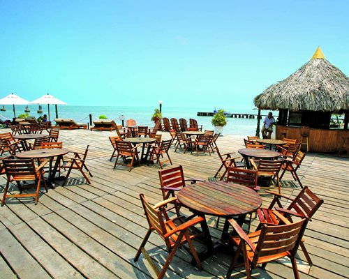 Outdoor restaurant with thatched covered bar alongside the beach.