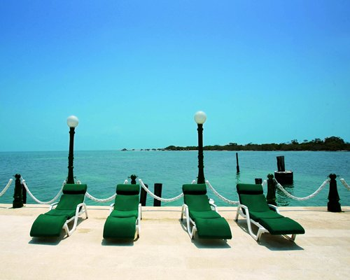 A view of chaise lounge chairs alongside the sea.