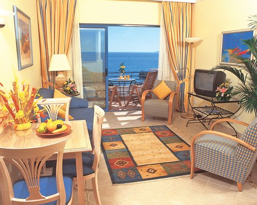 An open plan living room and dining room with a television and a balcony with beach view.