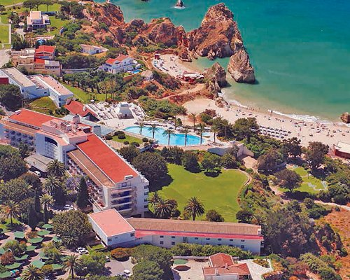 An aerial view of Pestana Alvor Beach Club with outdoor swimming pool and landscaping alongside the beach.