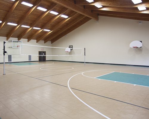 An indoor basketball court with a volleyball set up.