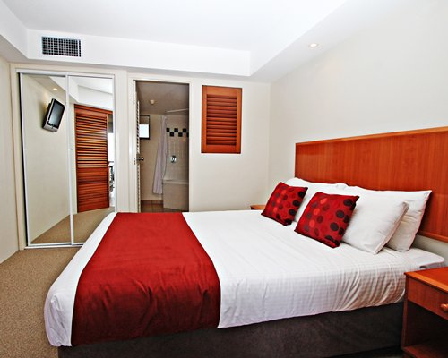 A well furnished bedroom with a queen bed and a bathroom.