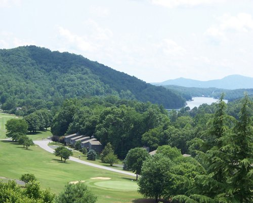 Golf course surrounded by wooded area alongside the mountains.