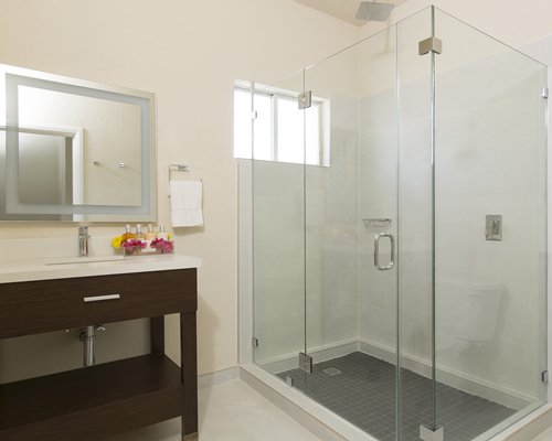 A bathroom with a stand up shower and single sink vanity.