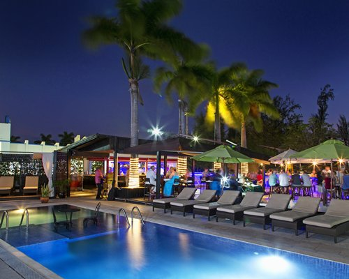 Night view of an outdoor swimming pool with chaise lounge chairs and poolside bars.