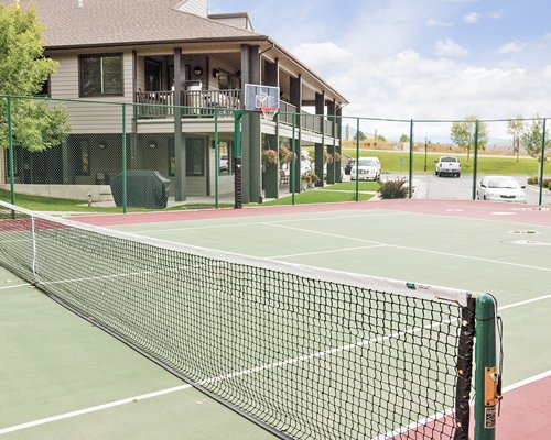 An outdoor tennis court alongside multi story resort units.