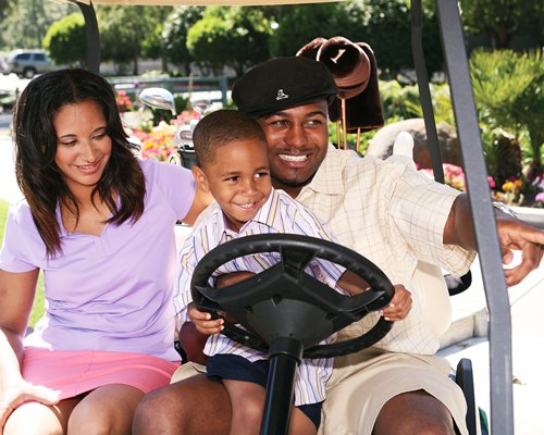 A view of family in the golf cart at the resort.