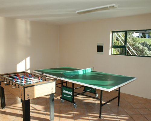An indoor recreational area with ping pong table and foosball.
