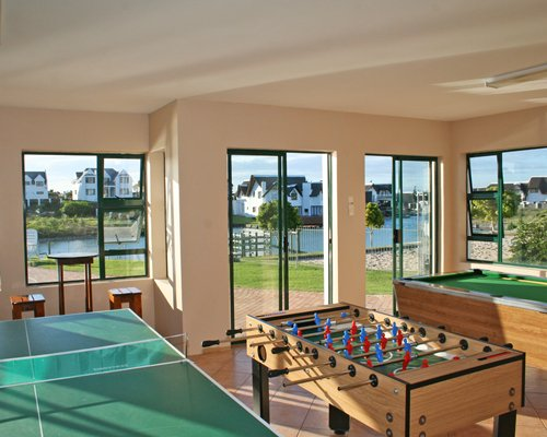 A recreational room with pool table ping pong foosball table and patio.