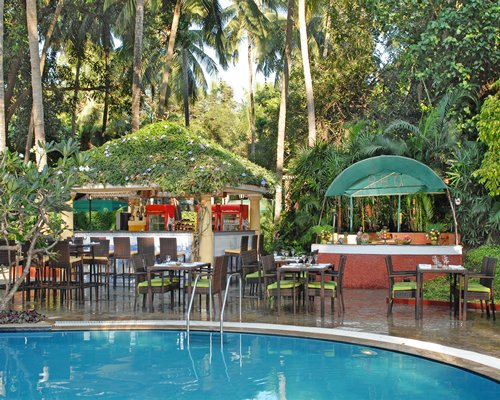 An outdoor fine dining area alongside the swimming pool.