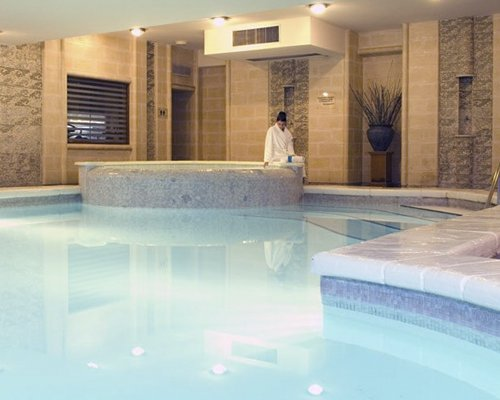 An indoor swimming pool with hot tub.