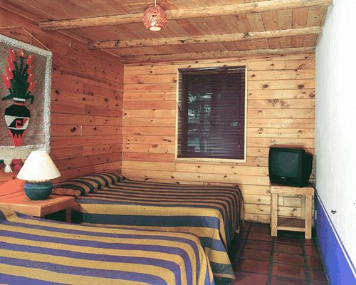 A well furnished bedroom with a double bed and a television.