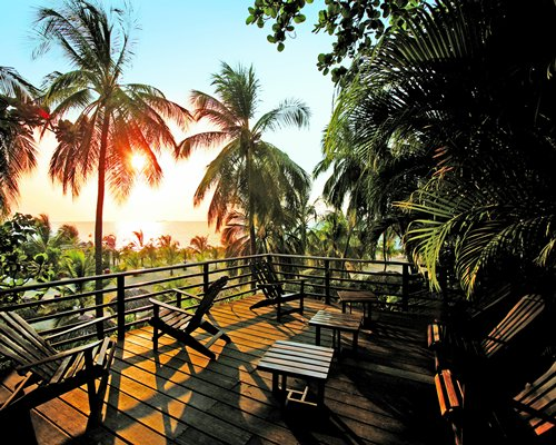 A balcony with patio furniture alongside coconut trees and the beach at dawn.