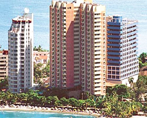 An exterior view of multi story resort units alongside the sea.