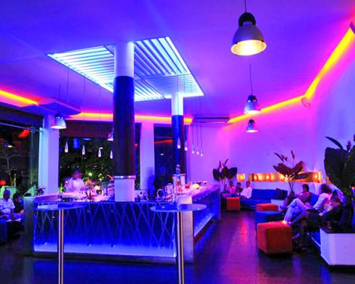 A view of an indoor bar with neon lighting.