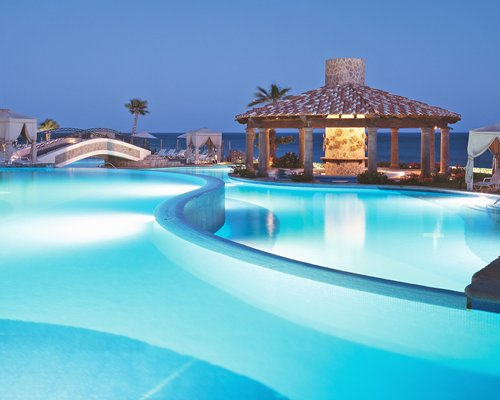 An outdoor swimming pool with poolside bar at night.