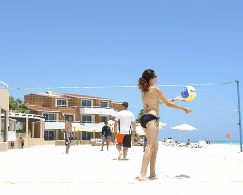 A view of the beach volleyball alongside chaise lounge chairs patio and sunshades.