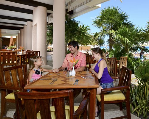 A family in an indoor fine dining area at the Sunset Fishermen Spa & Resort.