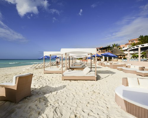 A view of the beach beds with chaise lounge chairs and sunshades alongside the sea.