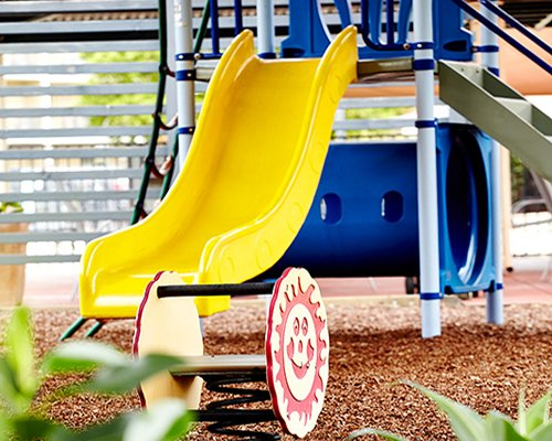 A view of an outdoor playscape with a slide.