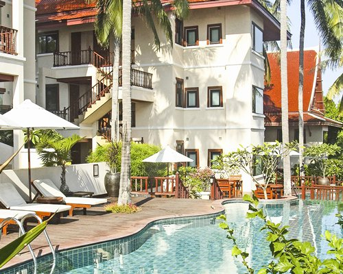 A scenic outdoor swimming pool with chaise lounge chairs and sunshades alongside multi story units.