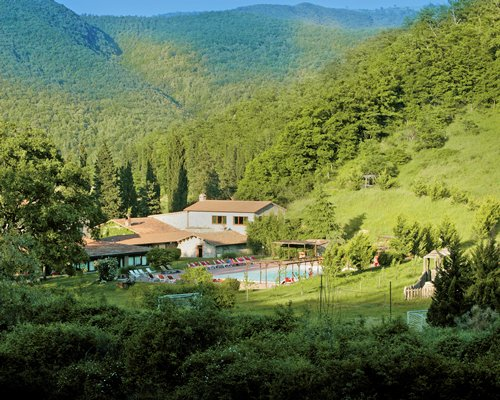 An exterior view of the La Casella resort surrounded by the wooded area and the mountains.