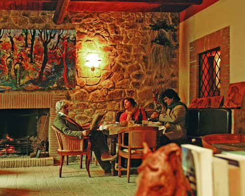 A family in an indoor restaurant with a fire in the stone fireplace.