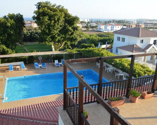 Balcony view of an outdoor swimming pool with chaise lounge chairs and patio furniture.
