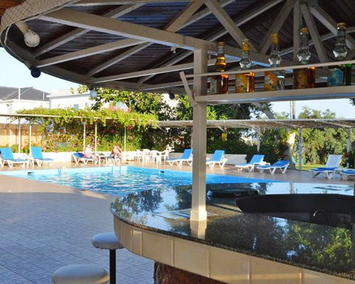 A poolside bar alongside the swimming pool with chaise lounge chairs.