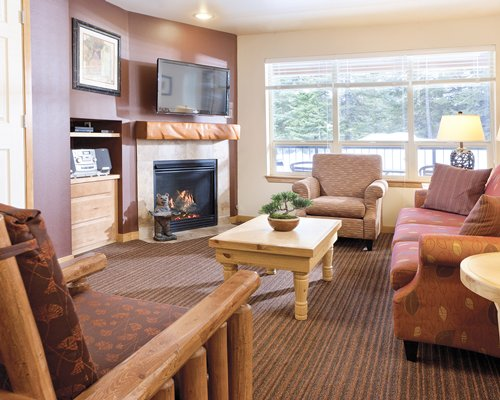 A well furnished living room with television fire in the fireplace and a balcony.