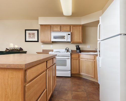 A well equipped kitchen with a microwave oven and refrigerator.