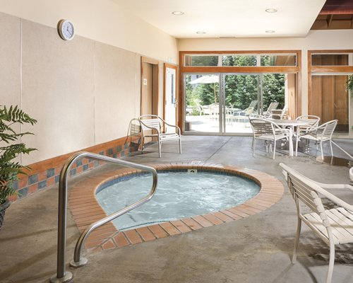 An indoor hot tub with patio furniture.