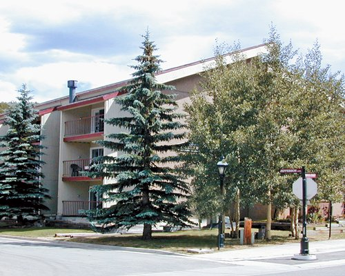 An exterior view of the Alpenrose Condominiums with the pine trees.