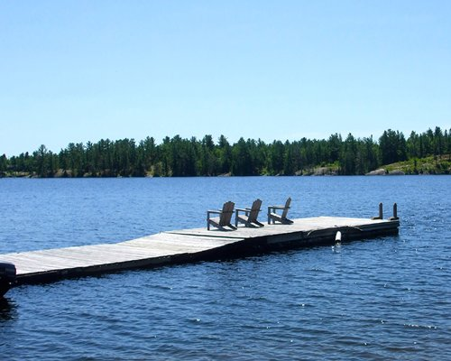 A view of the wooden pier with chaise lounge chairs leading to the lake.