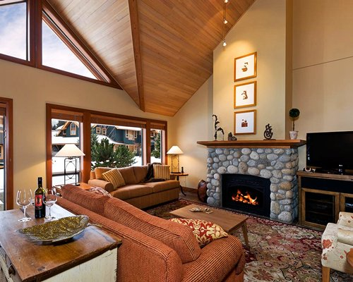 A well furnished living room with a television fire in the stone fireplace and outside view.